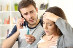 Man helping his wife calling doctor on phone Royalty Free Stock Photography