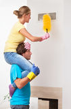 Man helping his wife in cleaning Stock Photos