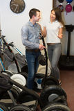 Man helping positive girl to select segway Royalty Free Stock Photography