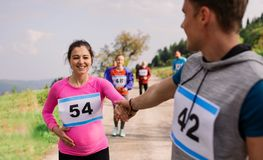 A man helping a pregnant woman in running competition in nature. royalty free stock photo
