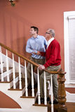 Man helping senior father climb stairs at home. Man helping senior father climb staircase at home Royalty Free Stock Images