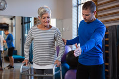 Man helping senior woman to walk with walker. Man helping senior women to walk with walker in hospital Royalty Free Stock Images