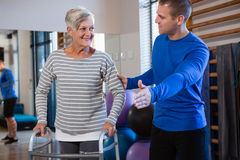 Man helping senior woman to walk with walker. Man helping senior women to walk with walker in hospital Royalty Free Stock Photos