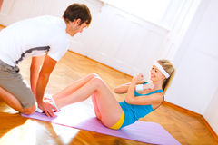 Man helping slim girl making abdominal crunch Stock Images