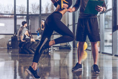 Man helping sportive woman exercising with trx gym equipment Stock Photos