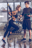 Man helping sportive woman exercising with trx gym equipment. Side view of men helping sportive women exercising with trx gym equipment Royalty Free Stock Image