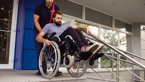 Free Man Helping To Move Down To A Disabled Man Royalty Free Stock Image - 128870026