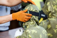 Man is helping to put on paintball mask for a boy. Paintball game stock photos