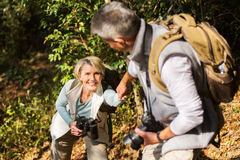 Man helping wife climbing mountain Royalty Free Stock Photography
