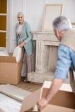 Man helping wife unpacking cardboard boxes Royalty Free Stock Photo