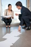 Man Helping Woman Collect Fallen Documents Royalty Free Stock Image