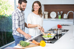 Man helping woman in cooking food Royalty Free Stock Photography