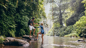 Man helping woman crossing stream. Couple outdoors on hike with men assisting women across stream. Young couple in forest crossing the creek Stock Image