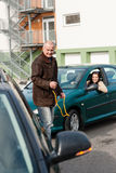Man helping woman with her broken car. Man helping women with her broken car problem breakdown cable Royalty Free Stock Photography