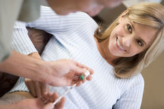 Man helping woman inject drugs to prepare for IVF. Treatment at home Stock Photos