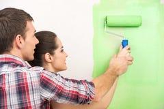 Man helping woman paint wall. Stock Image