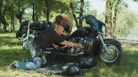 Man helping woman to repair motorbike outdoors. Brutal male biker helping pretty woman to repair broken motorcycle and teaching her which wrench to use during stock video