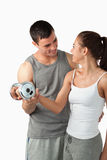 A man helping a woman to work out. Portrait of a men helping a young women to work out against a white background Stock Images