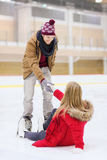 Man helping women to rise up on skating rink Royalty Free Stock Images