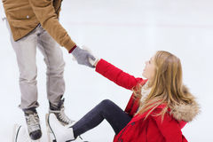 Man helping women to rise up on skating rink Stock Images