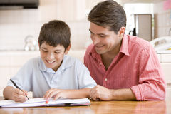 Man helping young boy in kitchen doing homework an Stock Images