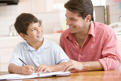 Man helping young boy in kitchen doing homework an Stock Photo