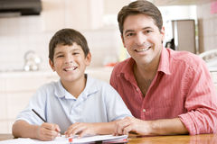Man helping young boy in kitchen doing homework an Royalty Free Stock Photos