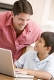 Man helping young boy in kitchen with laptop Stock Photo