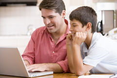 Man helping young boy in kitchen with laptop Stock Photos