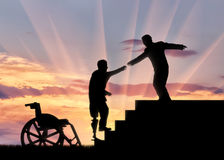 Man helps disabled person with prosthesis on stairs on sunset Royalty Free Stock Photography