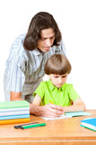 A man helps first graders how to write in a notebook Stock Photography
