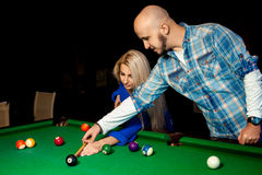 Man helps a girl to play pool on the billiard table Stock Photography