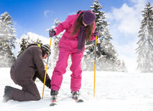 Man helps her girlfriend to put her skis Royalty Free Stock Image