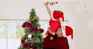 Man helps his son decorating christmas tree stock footage