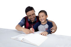 Man helps his son doing homework. Young men helps son doing homework with book on the table, isolated on white background royalty free stock images
