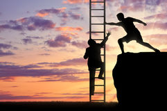 Man helps a person to climb the stairs. ?an helps a person to climb the stairs. Concept of teamwork Stock Photos