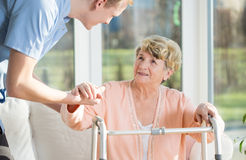 Man helps to stand up an older woman. Man helps to stand up an older women at nursing home Royalty Free Stock Photo