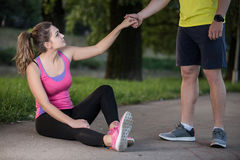 Man helps to woman with injured knee at sport activity Stock Image