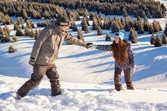 Man helps woman climbs on top of the mountain Stock Photos