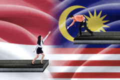 Man helps woman with indonesian and malaysian flags Stock Image