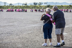 Man Helps Woman Put on Survivor Sash at Breast Cancer Walk Stock Photography