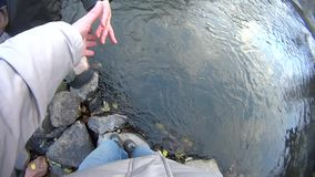 Man helps a woman to cross a river stock footage