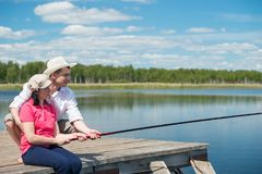 Man helps a woman to fish in nature Royalty Free Stock Photo