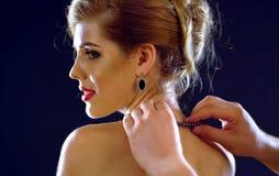 Man helps woman to wear jewelery. Royalty Free Stock Photos