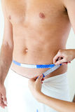 Man with a helthy body measuring his stomach. Diet concept. Royalty Free Stock Photos