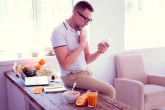 Bearded mature man wearing glasses hesitating about drinking food supplements. Man hesitating. Bearded mature man wearing glasses hesitating about drinking food stock photo