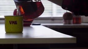 Man het glastheepot van de handholding met hete thee giet het in grote mok stock videobeelden