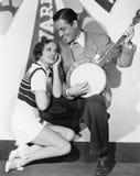 Man het spelen banjo voor het aanbidden van vrouw (Alle afgeschilderde personen leven niet langer en geen landgoed bestaat Levera Royalty-vrije Stock Foto's
