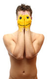 Man hide his face under smile mask stock photo