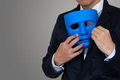 Man hide mask. Businessman is hiding blue mask in your suit on gray background with clipping path and copy space Stock Photography
